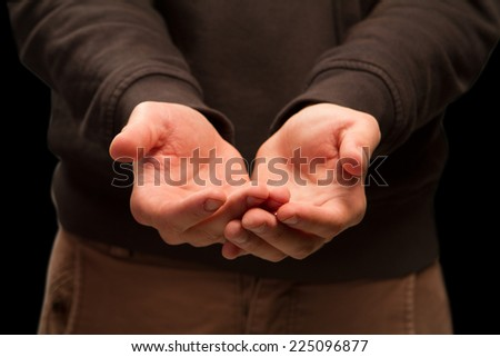 Open hands. Holding, giving, showing concept. Two man's hands in offering gesture against black background. waiting for the gift, money or bread.