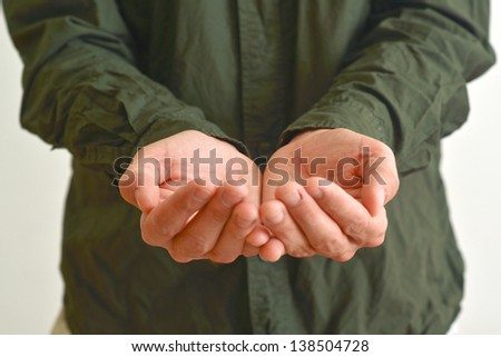 Open hands of a man hopefully held up. Cupped hands asking for something.