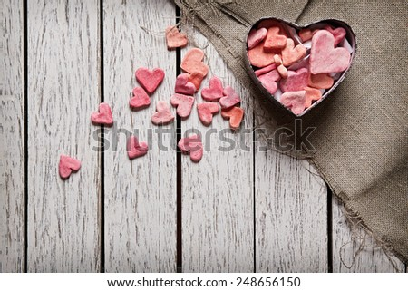 Open heart shaped gift box with heap of small hearts inside and outside on white wood table. - stock photo