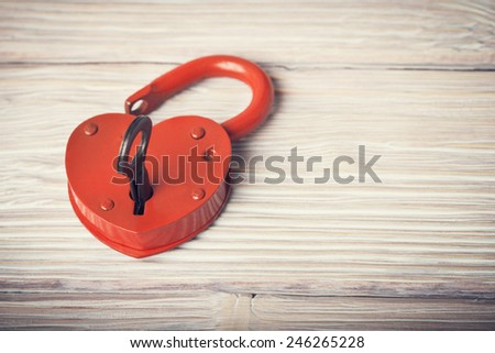 Open heart shaped lock and key over light vintage wooden background - stock photo