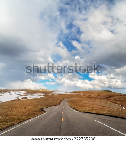 Open highway , high in the mountains with distant clouds, rocky mountains national park - stock photo