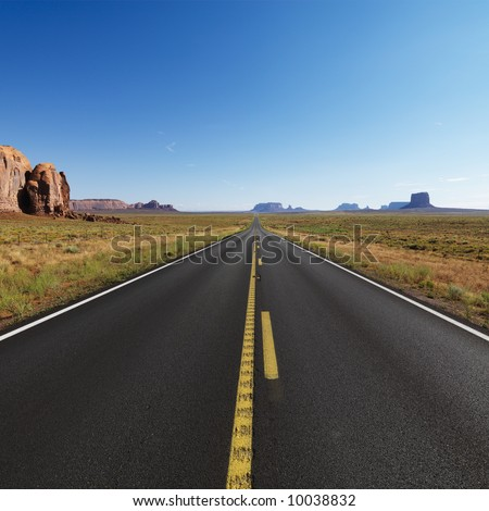 Open highway in scenic desert landscape with distant mountains and mesas.