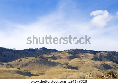Open hillside in the eastern foothills of the Rocky Mountains in late afternoon with long shadows and breezy clouds.  There are some homes in the lower right corner. - stock photo