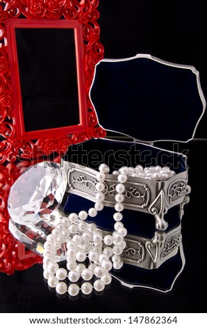Open jewelry box with pearls over black background.