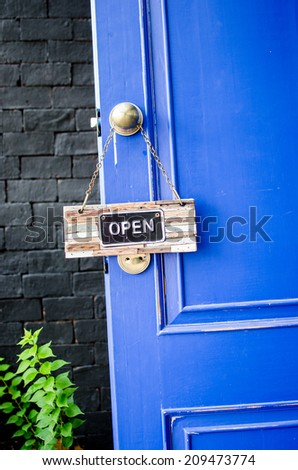 open label hanging on knob at blue door in garden - stock photo