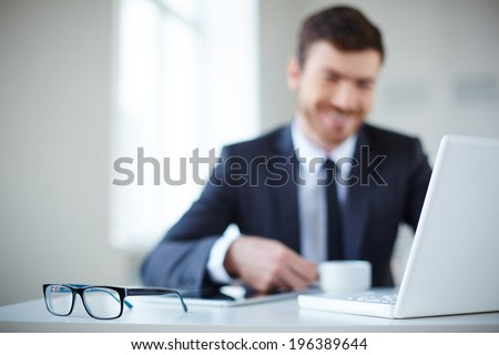 Open laptop and eyeglasses at workplace with businessman on background - stock photo
