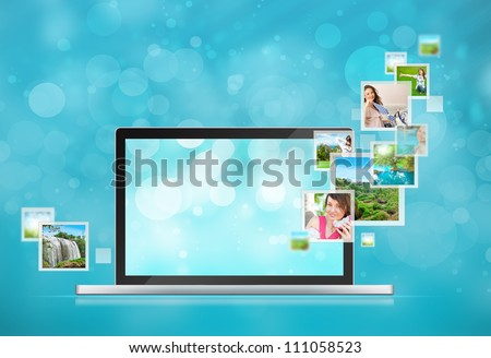 Open laptop at blue background. Pictures are flying out of the screen
