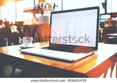 Open laptop computer and cup of coffee lying on a wooden table in cafe bar interior, portable net-book with copy space screen for your information content or text message, distance work via internet - stock photo