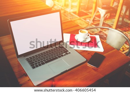 Open laptop computer and mobile phone with blank copy space screen for your information content or text message, portable net-book with cell telephone lying on a wooden table in modern coffee shop  - stock photo