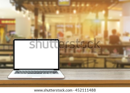 Open laptop computer  lying on a wooden table in cafe bar interior, portable net-book with copy space screen for your information content or text message, freelance ,internet,vintage color   - stock photo