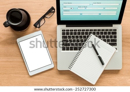 Open laptop shows blank information form and  digital tablet with isolate screen on wooden table. Blank diary on laptop, glasses and a cup of coffee on workspace. Top view image for mock up concept. - stock photo