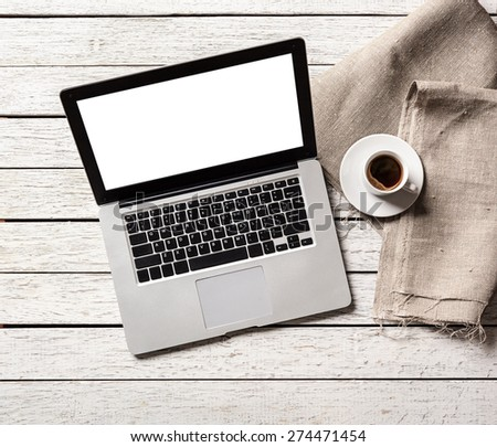 Open laptop with coffee cup on desktop. Clipping path included. - stock photo