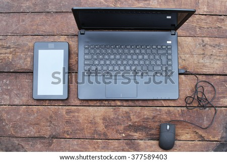 Open laptop with digital tablet computer and mouse on old wooden desk