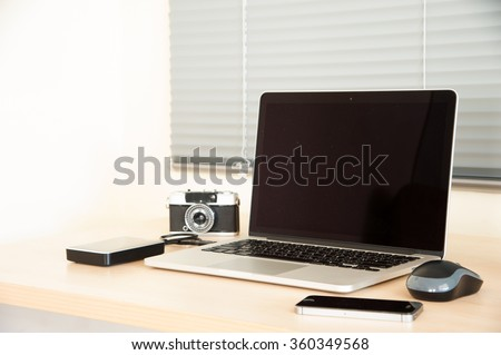 Open laptop with external hard drive,  mouse, camera, smart phone and cup  on wood table and blind. View from oblique front. - stock photo