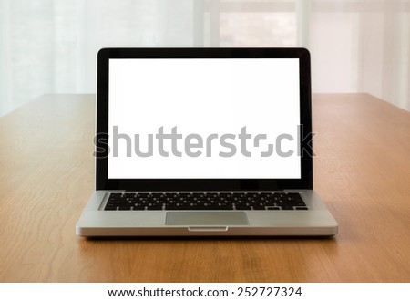 Open laptop with isolate screen on wooden desk with natural light coming through the window, Mock up concept and idea. - stock photo