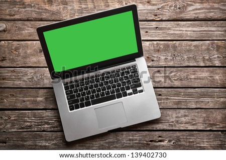 Open laptop with isolated green screen on old wooden desk. - stock photo