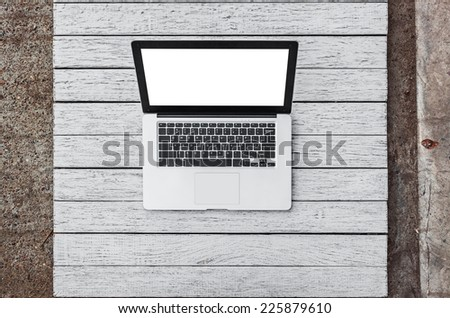 Open laptop with isolated screen on white old wooden desk. - stock photo