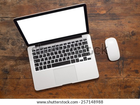 Open laptop with isolated white screen on old wooden desk. - stock photo