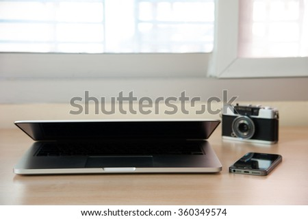 Open laptop with smart phone and camera on wood table. - stock photo