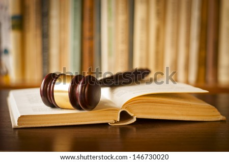 Open law book with a judges gavel resting on top of the pages in a courtroom or law enforcement office - stock photo