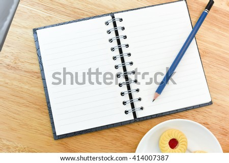 Open Leather Book and Pencil on  Wooden Table with white background.Have a cup of black coffee and smile cookie.