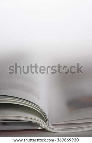 Open magazine on a table with shallow depth of field - stock photo