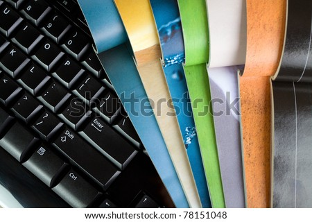 Open magazines and computer keyboard, new media and technology - stock photo