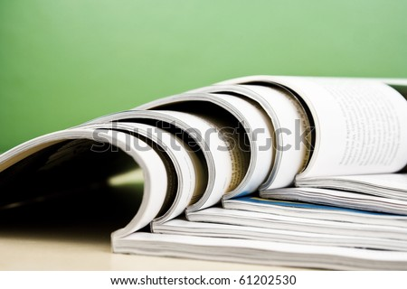 Open magazines in composition lying on table on green background