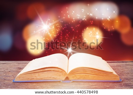 Open magic book on wooden background - stock photo