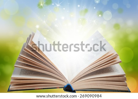 Open magic book with light and blur effects on green background - stock photo