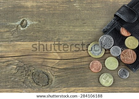 Open Male Black Leather Wallet With British Different Coins On Old Rough Brown Wood Background With Copy Space - stock photo