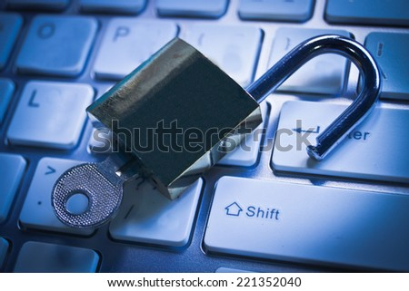 open metal lock with key on computer keyboard - security concept in computer - stock photo