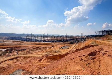 open mining pit with heavy machinery - stock photo