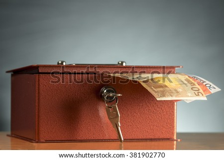 Open money box with several euro banknotes sticking out - stock photo