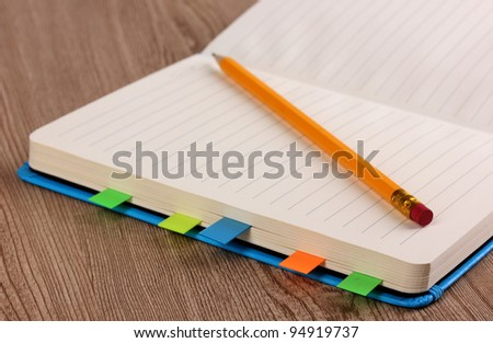 Open note book with stickies and pencil close-up on wooden background - stock photo
