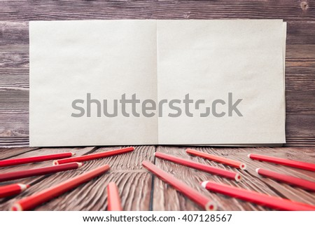 Open note pad and red pencils over old wooden background