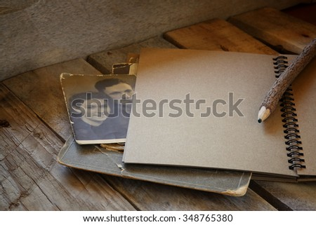 open notebook and antique photos on wooden table. retro filtered   - stock photo