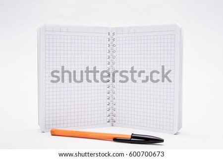 Open notebook and ball pen on a white background