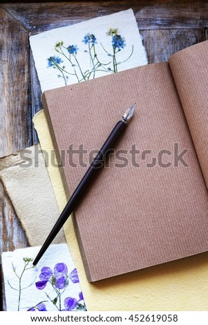 Open notebook and paper cards with dried flowers on wooden table.