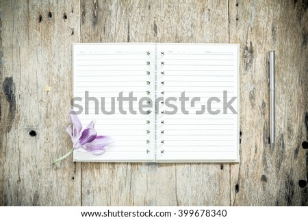 Open Notebook and pen on old wooden background. - stock photo