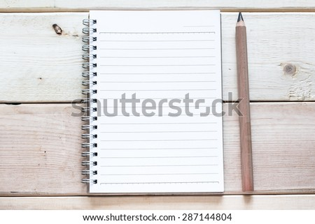 open notebook and pencil on wood table - stock photo
