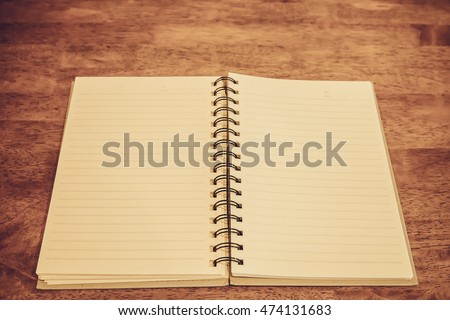 Open notebook blank pages on wooden table vintage style