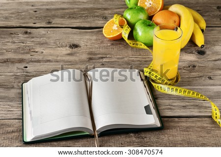 Open notebook for notes of fruit (apple, orange, banana) and orange juice on a wooden table. The concept of a healthy lifestyle and losing weight. Free space for text. Copy space. Top view - stock photo