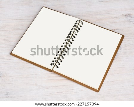 Open notebook isolated on wooden background - stock photo