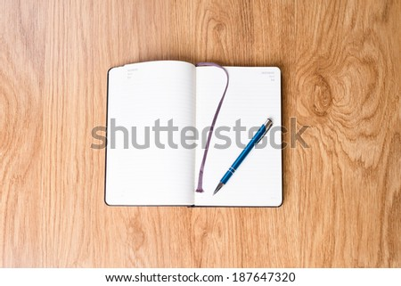 Open notebook on a desk. Front of the planner is blank. - stock photo