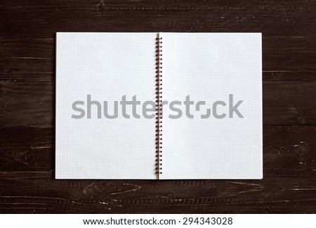 Open notebook on dark wooden table. - stock photo