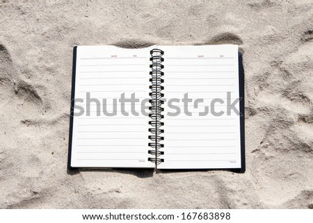 Open notebook on the beach. - stock photo