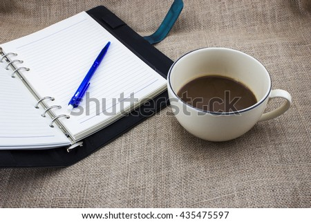 Open notebook, pen and cup of coffee