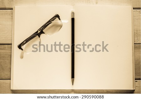 open notebook , pencil and eyeglasses on wood table ( antique style ) - stock photo