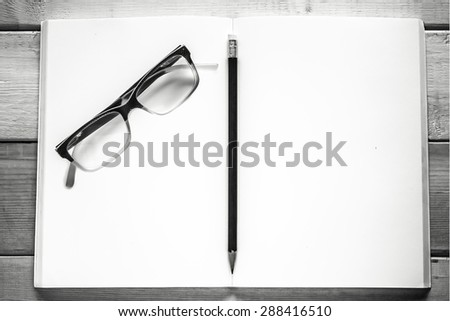 open notebook , pencil and eyeglasses on wood table ( black and white style ) - stock photo